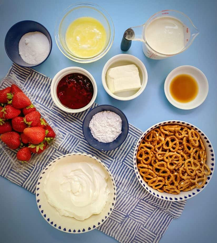 ingredients for making healthy berry yogurt pie without cool whip on a blue tabletop