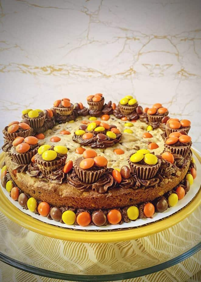 yellow plate with a chocolate peanut butter cookie cake decorated with brown, yellow and orange candies