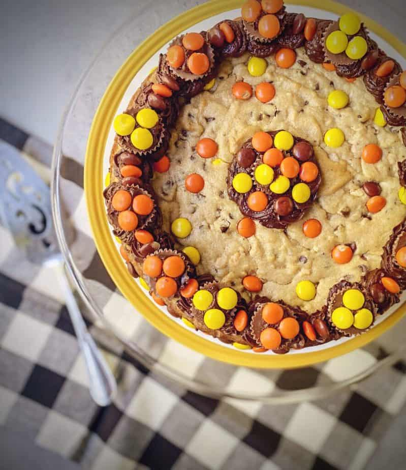 overhead shot of chocolate chip peanut butter cookie cake with a black and white gingham napkin and silver pie server