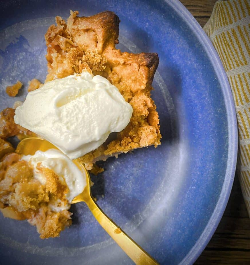 blue pasta bowl with a slice of peach crumble pie a la mode with a gold spoon taking a bite