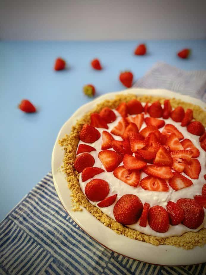 close up shot of yogurt pie decorated with fresh strawberries