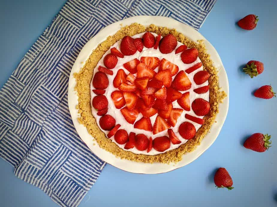 flat-lay shot of strawberry yogurt pie with pretzel crust on a blue table with a blue and white striped cloth