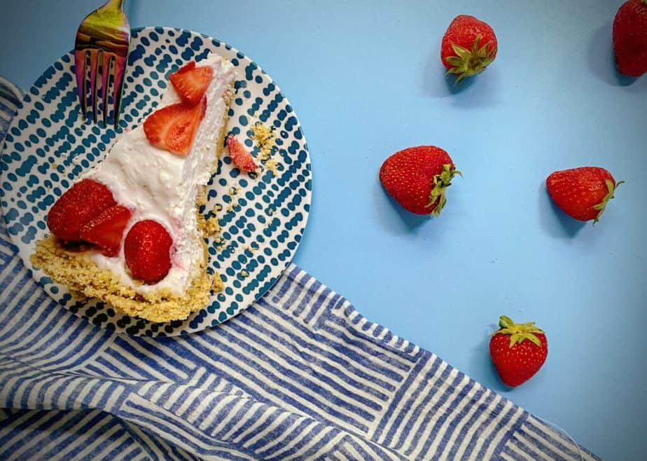 flat lay shot of a slice of berry yogurt pie on a blue and white tablescape