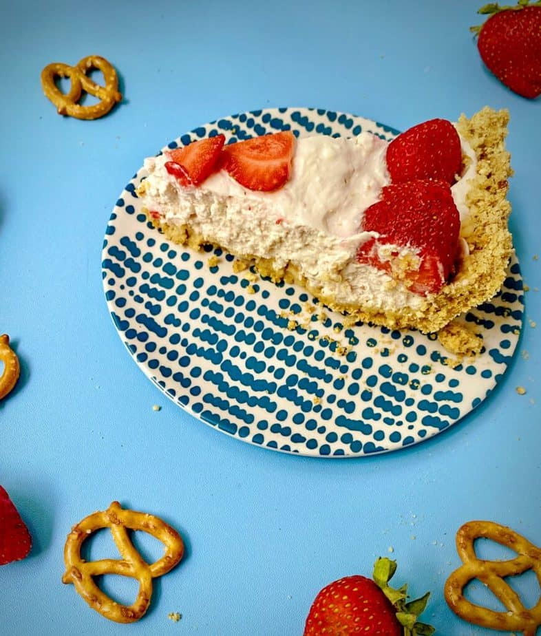 slice of yogurt pie on a blue and white plate with pretzels and whole berries strewn about