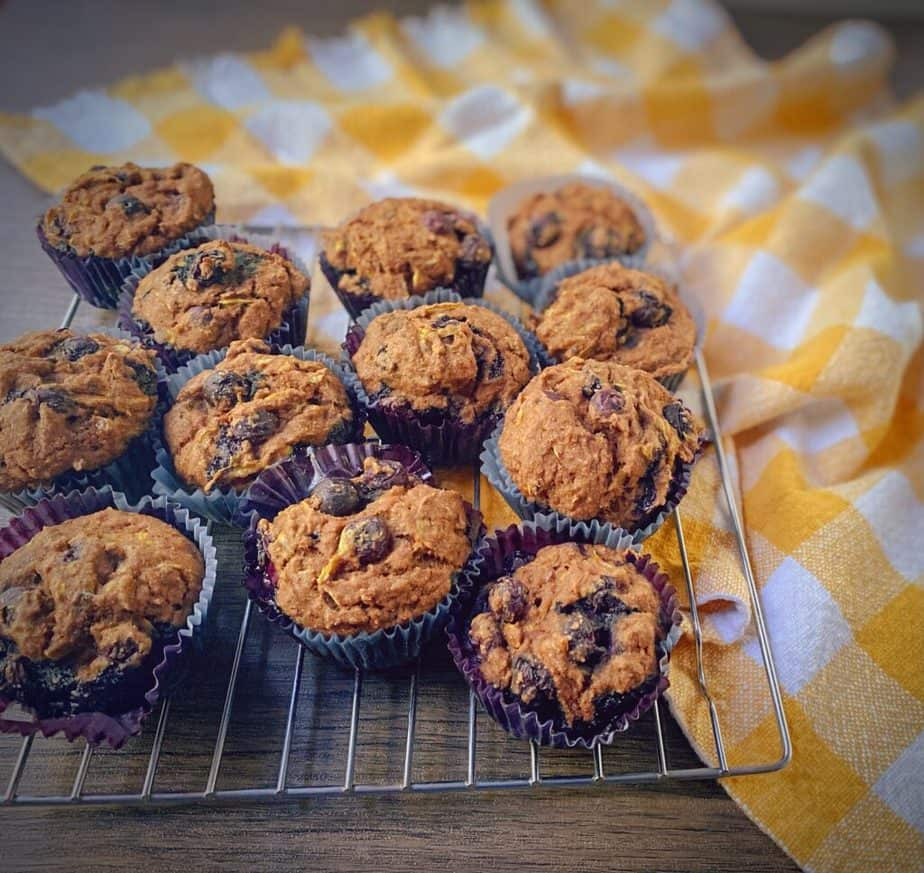 healthy whole wheat summer squash and blueberry muffins cooling on a rack with a yellow gingham dish towel