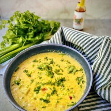 bowl of corn chowder on a table with a bottle of hot sauce and a striped green and white towel