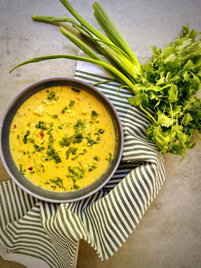 overhead shot of a bowl of corn chowder with a bunch of cilantro and bunch of scallions on a grey table with a striped towel