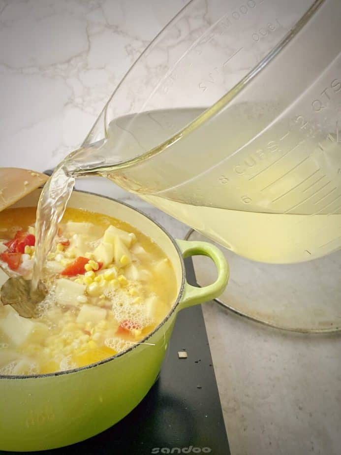 pouring in corn stock to corn chowder pot