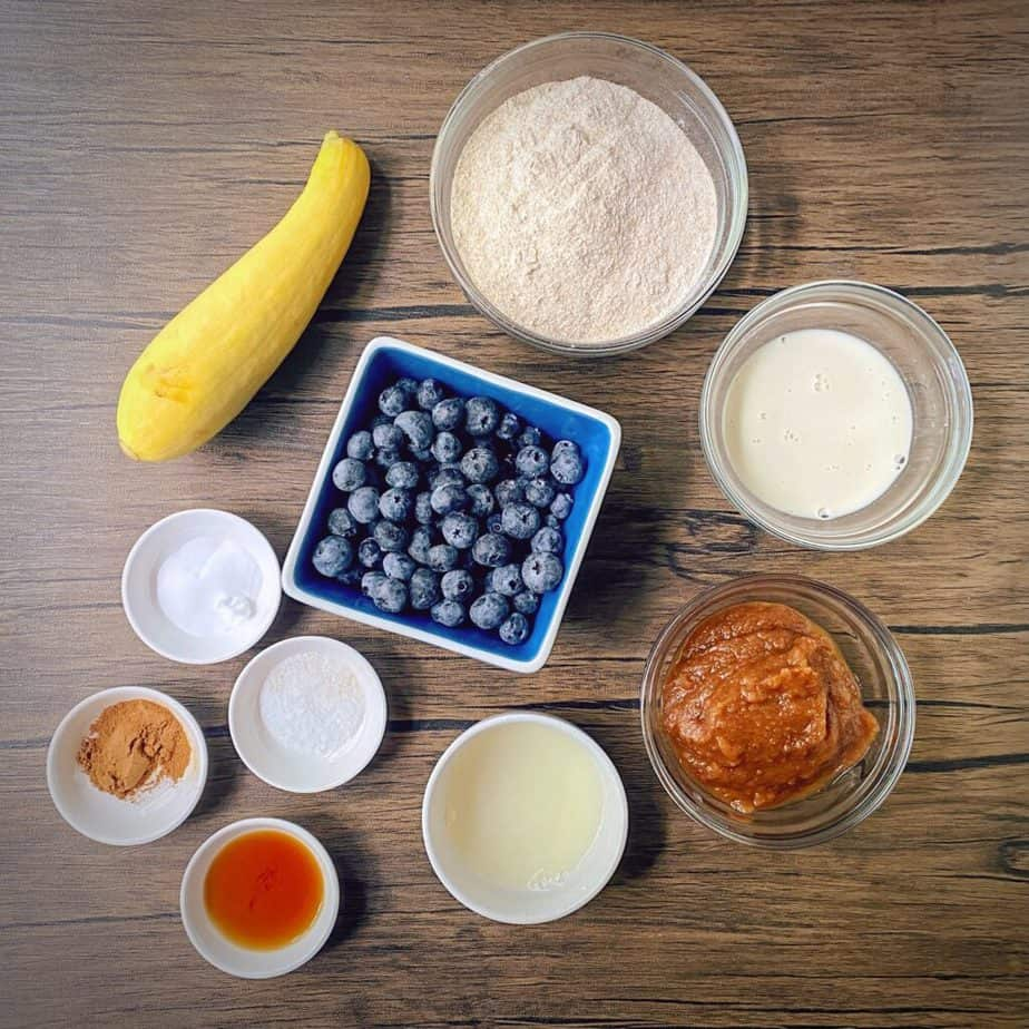 ingredients for making summer squash muffins measured into bowls and laid out on a table