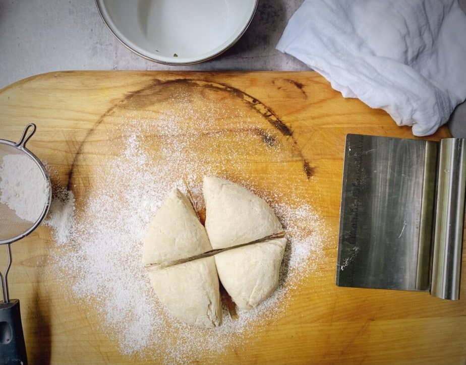 cutting rested dough into 4 even portions on a floured work surface