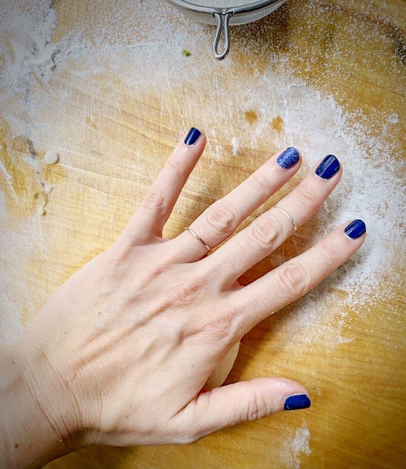 palm of hand smooshing nautilus down into a pancake