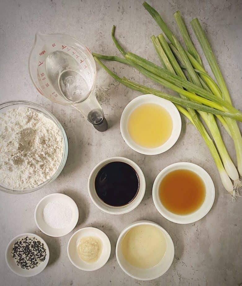 ingredients for making Chinese scallion pancakes and dipping sauce measured out in small bowls on a grey table