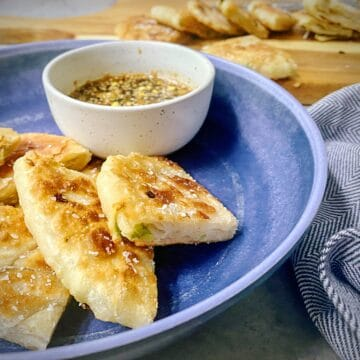 blue pasta bowl with quartered chinese scallion pancakes and a ramekin of dipping sauce