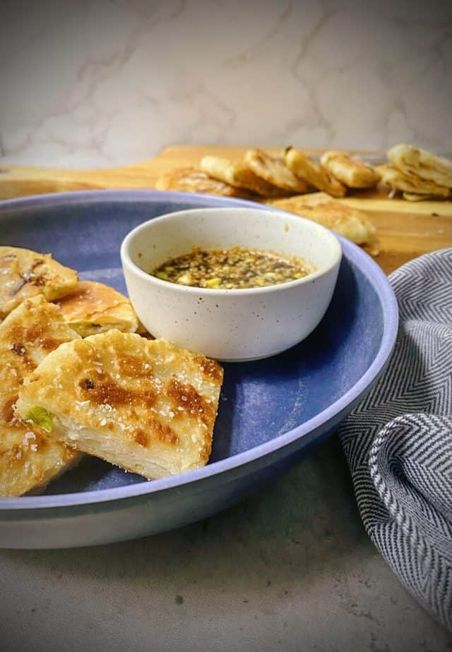 serving bowl of scallion pancakes with dipping sauce in a ramekin and a blue and white chevron patterned napkin