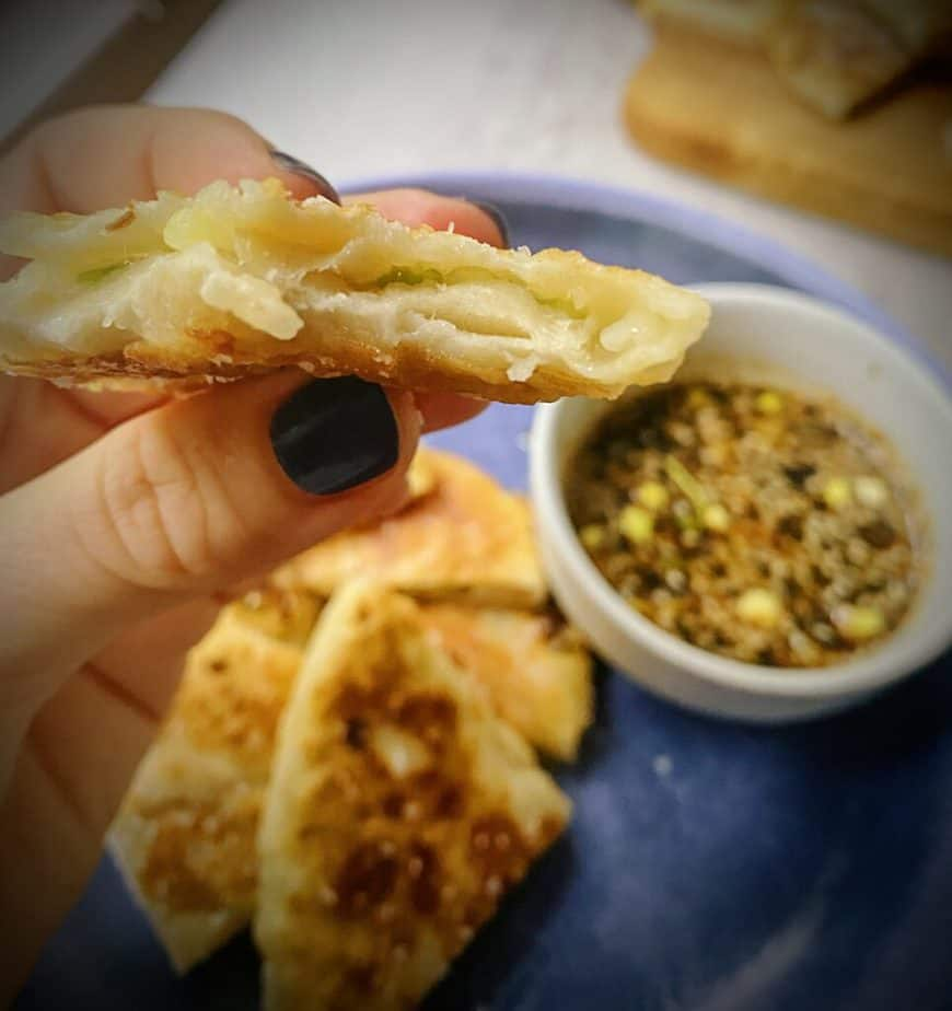 hand holding quarter of scallion pancake to show lamination of dough - there are so many layers!