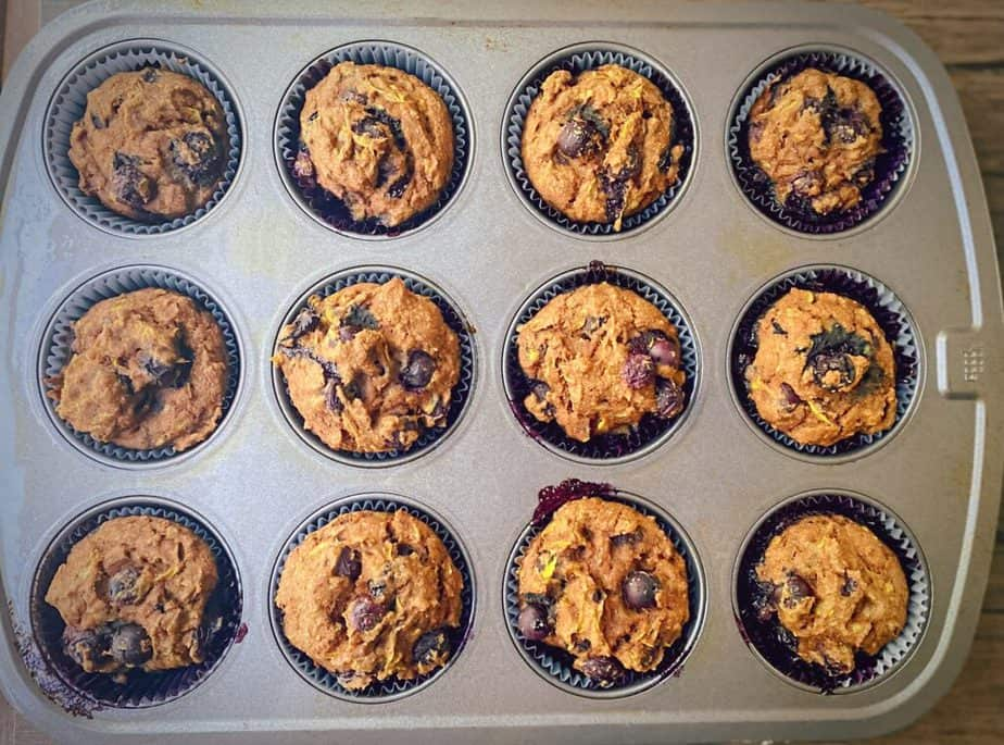 tin of a dozen baked whole wheat squash muffins with blueberries