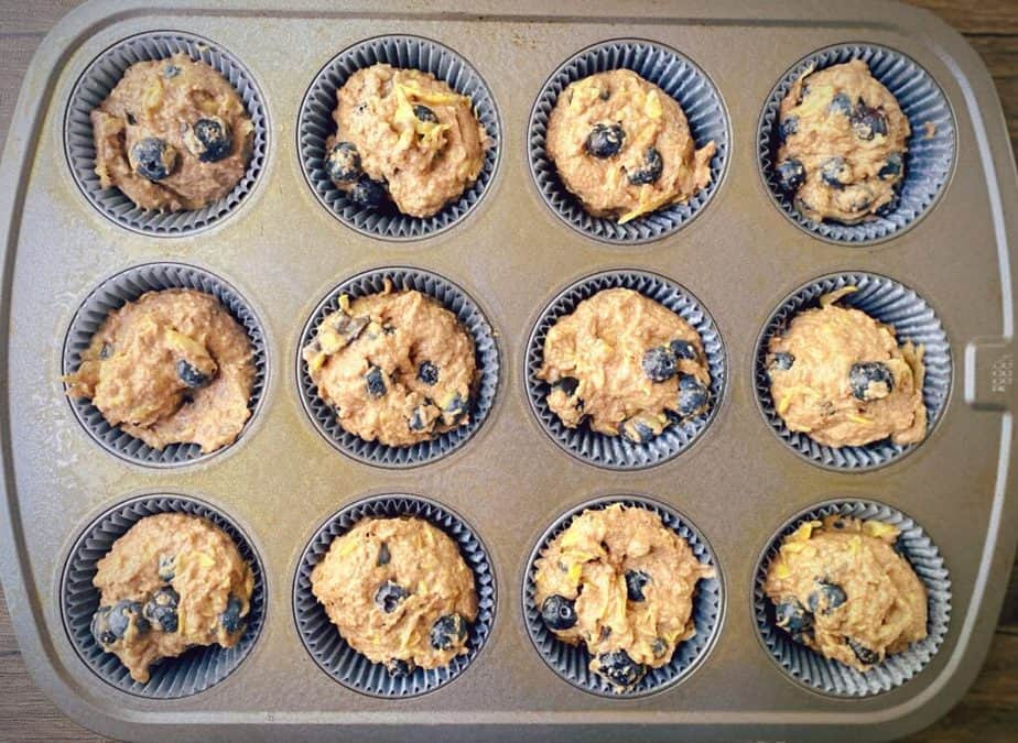 overhead shot of unbaked muffins in a baking tin