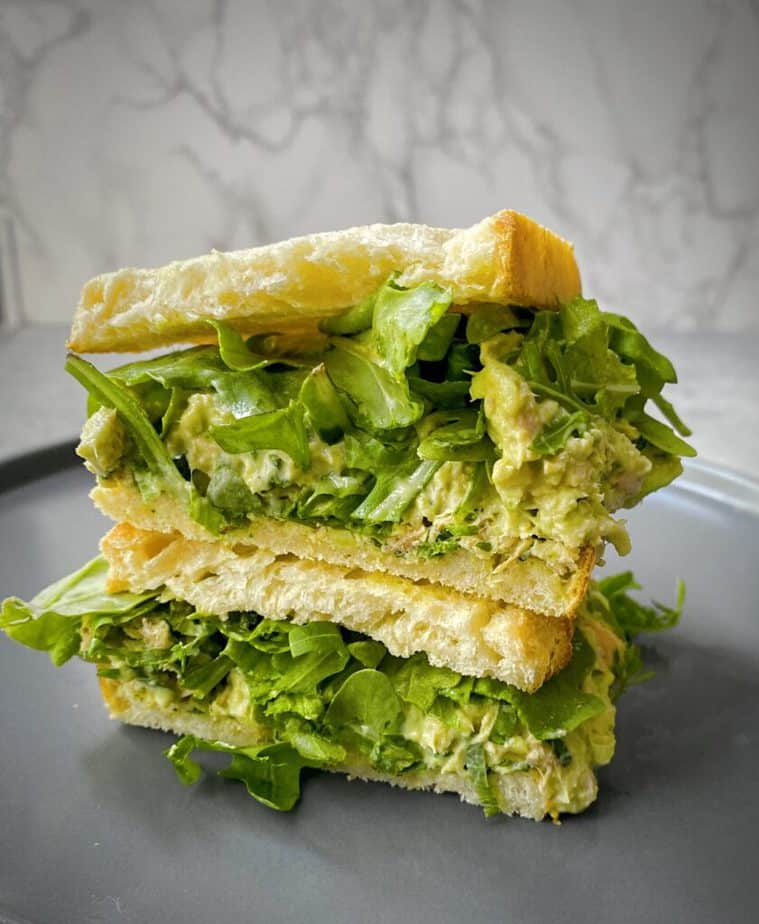 stacked halves of a tuna and avocado salad sandwich on toasted sourdough with arugula