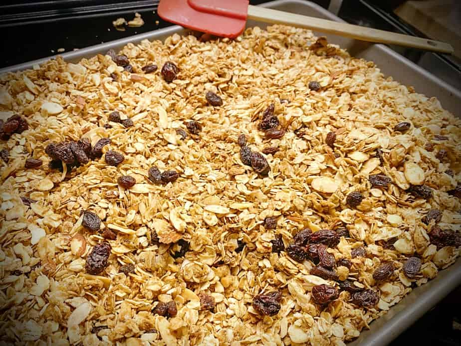 half of big batch baked granola on a sheet pan atop the oven