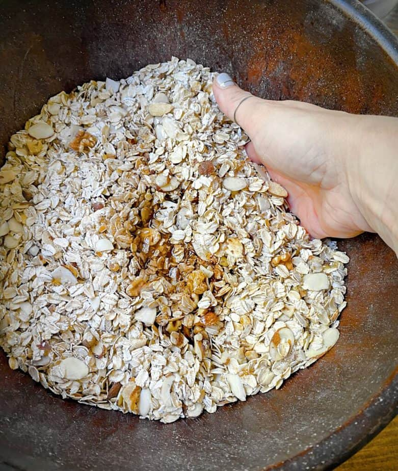 hand mixing wet and dry granola ingredients