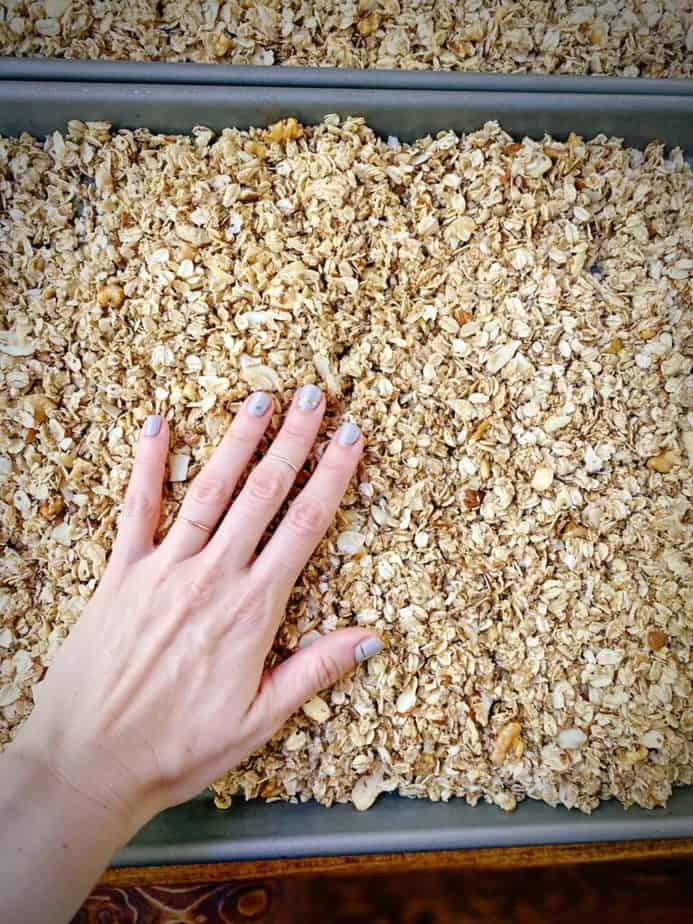 hand patting the unbaked granola into a single layer